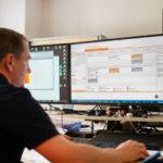 Techniker überwacht automaisierte Anmeldung und Disposition der LKW Anlaieferungen am Monitor des Logistikleitsystem BLS